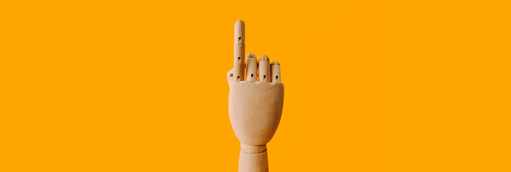 Trähand som håller upp pekfingret mot gul bakgrund